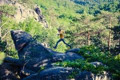 Un homme saute sur une montagne Photos libres de droits