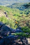Un homme saute sur une montagne Photo libre de droits