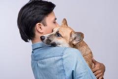 Un homme se blottissant et étreignant son chien, amitié étroite aimant dedans Photographie stock