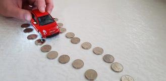 Un homme se déplace avec dans son jouet rouge d'abarth de Fiat 500 de doigts sur la ligne de route faite de pièces de monnaie isr photos stock