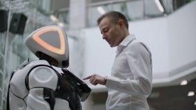 Un homme se tient avec un bot de robot et lui pose des questions et demande l'aide en cliquant sur sur l'écran sur le corps de ro banque de vidéos
