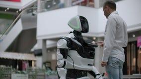 Un homme se tient avec un bot de robot et lui pose des questions et demande l'aide en cliquant sur sur l'écran sur le corps de ro clips vidéos