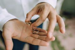 Un homme se tient dans des ses mains sur les paumes des anneaux d'or de mariage Plan rapproché Image libre de droits