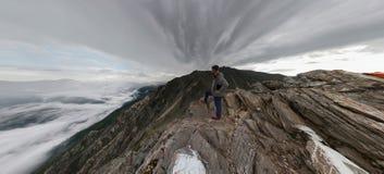Un homme se tient dans les montagnes et examine la distance, en haut photo libre de droits