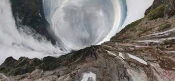Un homme se tient dans les montagnes et examine la distance, en haut photos libres de droits