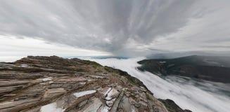 Un homme se tient dans les montagnes et examine la distance, en haut Images libres de droits