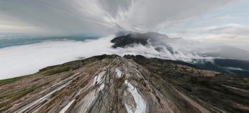 Un homme se tient dans les montagnes et examine la distance, en haut Images stock