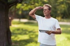 Un homme se tient en parc avec un comprimé gris dans des ses mains Il recherche quelqu'un Photo libre de droits