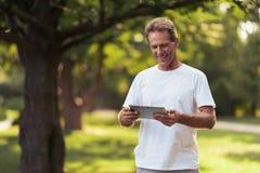 Un homme se tient en parc avec un comprimé gris dans des ses mains Il regarde l'écran de comprimé Photographie stock