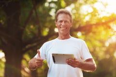Un homme se tient en parc avec un comprimé gris dans des ses mains Il regarde l'appareil-photo et montre des pouces  Images stock