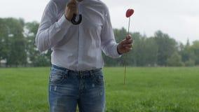 Un homme se tient sous un parapluie, il le ` s pleuvant et tournoyant dans des ses mains un coeur rose, l'homosexualité, le conce clips vidéos