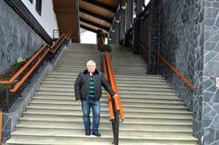 Un homme se tient sur l'escalier que cela mène aux ascenseurs photo stock