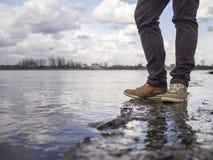 Un homme se tient sur le bord à côté de l'eau Photographie stock libre de droits