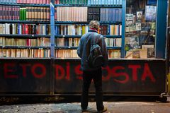 Un homme semble curieux au sujet des titres des livres Photo stock