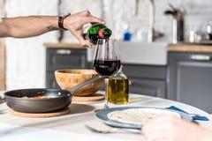 Un homme servant le vin rouge dans un verre à la maison Photographie stock