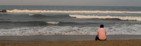 Un homme seul s'asseyant sur la plage images stock