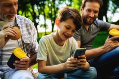 Un homme, son père plus âgé et fils s'asseyent en parc sur un pique-nique Un garçon s'assied avec un smartphone dans des ses main Photographie stock