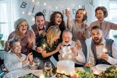 Un homme supérieur avec la famille sur plusieurs générations célébrant l'anniversaire sur la partie d'intérieur photos libres de droits