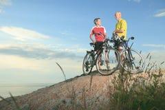 Un homme supérieur et une femme font du vélo le coucher du soleil Images libres de droits