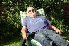 Un homme supérieur heureux se trouvant sur un lit pliant Image stock
