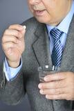 Un homme supérieur prenant la médecine avec un verre de l'eau Photographie stock libre de droits
