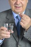 Un homme supérieur prenant la médecine avec un verre de l'eau Image libre de droits