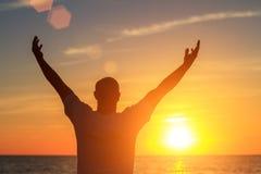 Un homme sur la plage au coucher du soleil montre à ses mains à quel point il heureux est avec le concept du voyage et de la rela Image libre de droits