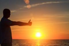 Un homme sur la plage au coucher du soleil montre à ses mains à quel point il heureux est avec le concept du voyage et de la rela Photo stock