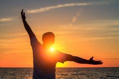 Un homme sur la plage au coucher du soleil montre à ses mains à quel point il heureux est avec le concept du voyage et de la rela Photos stock