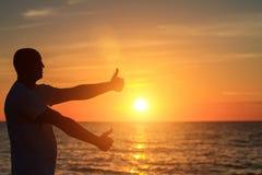 Un homme sur la plage au coucher du soleil montre à ses mains à quel point il heureux est avec le concept du voyage et de la rela Photo libre de droits