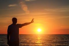 Un homme sur la plage au coucher du soleil montre à ses mains à quel point il heureux est avec le concept du voyage et de la rela Photographie stock libre de droits