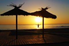 Un homme sur la plage fait bon accueil au lever de soleil Des mains sont répandues à part photo libre de droits