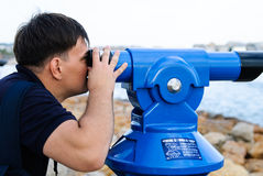 Un homme sur le rivage regardant la mer avec des jumelles Photographie stock libre de droits