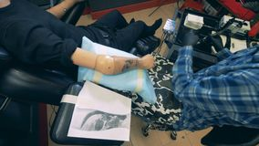Un homme tatouant une main prosthétique d'un handicapé clips vidéos