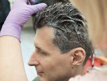 Un homme teint ses cheveux dans le salon de beauté photographie stock libre de droits
