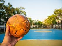 Un homme tenant un ballon de football jaune sur un terrain de football bleu photo stock