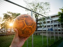 Un homme tenant un ballon de football jaune sur un terrain de football bleu images libres de droits
