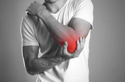 Un homme tenant des mains Douleur dans le coude Le foyer est highlighte image stock
