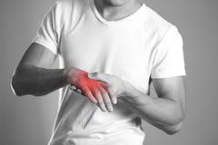 Un homme tenant des mains La douleur dans le poignet le foyer est highlighte image libre de droits