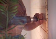 Un homme tenant un foret et faisant un trou dans le bois Image libre de droits