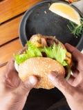 Un homme tenant le double hamburger avec le lectuce c de poivron doux d'oignon photographie stock libre de droits