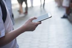 Un homme tenant un téléphone portable image stock