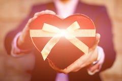 Un homme tenant un boîte-cadeau rouge comme coeur pour son amie Image libre de droits