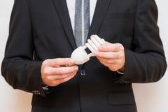 Un homme tenant une ampoule économiseuse d'énergie image libre de droits
