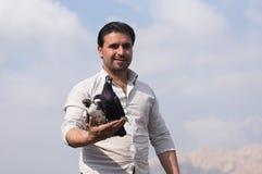 Un homme tenant une colombe avec fierté Photographie stock