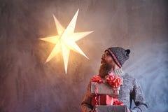 Un homme tient des cadeaux de Noël photographie stock libre de droits