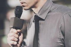 Un homme tient un microphone et parle dans lui Images stock