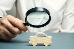 Un homme tient une loupe au-dessus d'une voiture en bois miniature Le coût estimatif de l'automobile Analyse et inspection techni photographie stock libre de droits