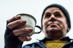 Un homme tient une tasse dans une main tendue Photographie stock