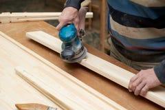 Un homme traite un produit en bois avec une machine de meulage photos stock